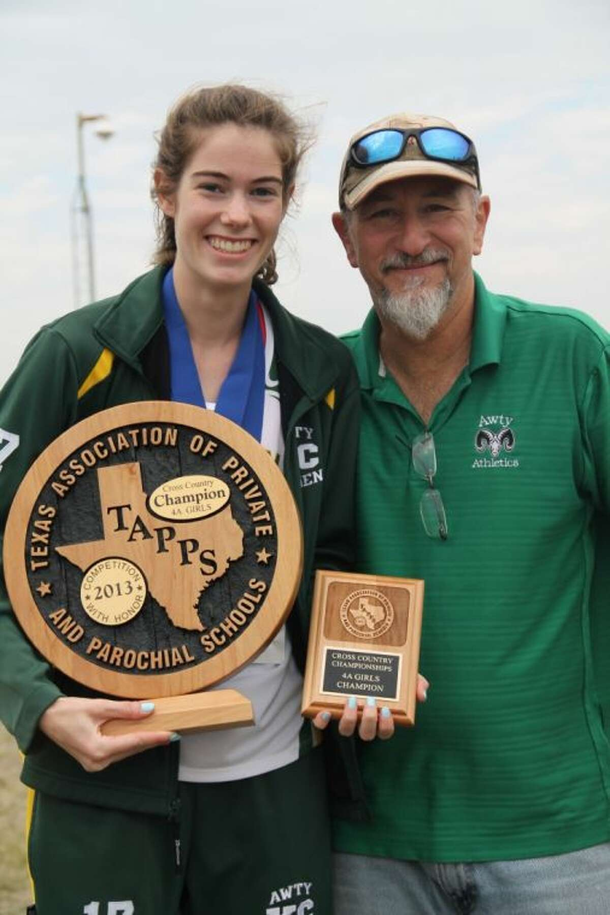 Awty International senior Isabelle Grant, shown with Awty International cross country head coach Robert Sload, holds both the individual plaque she received for winning the TAPPS 4A girls cross country state championship Saturday morning and the team award, the Lady Rams earned by winning the state championship.