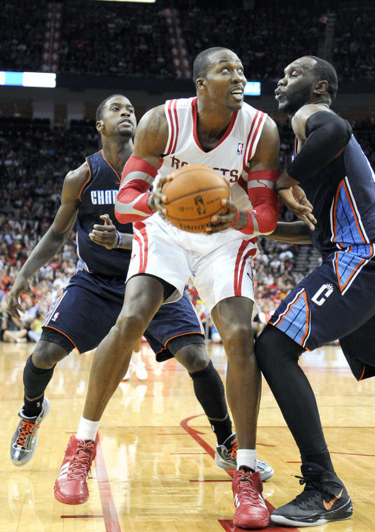 Houston Rockets center Dwight Howard looks to the basket between Charlotte Bobcats defenders Michael Kidd-Gilchrist, left, and Al Jefferson in the second half Wednesday in Houston.