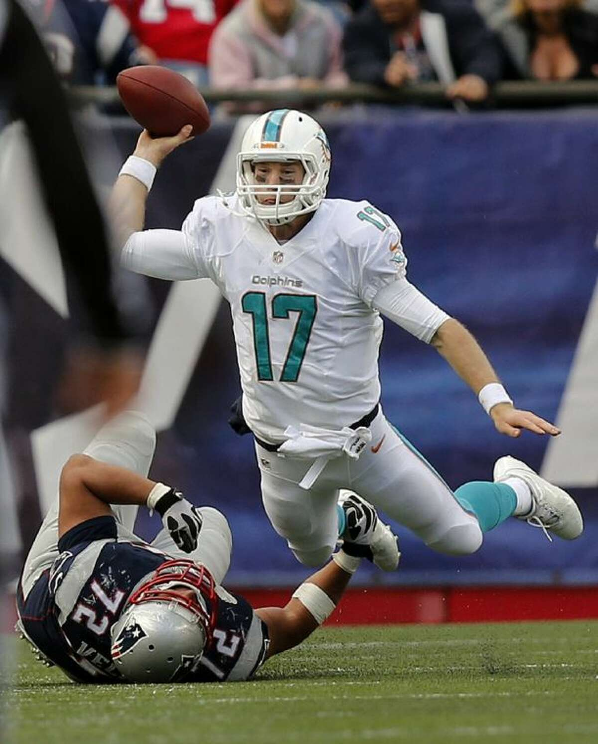 Miami Dolphins quarterback Ryan Tannehill gets rid of the ball as he is tackled by New England Patriots defensive tackle Joe Vellano on Sunday in Foxborough, Mass. The Patriots won 27-17.