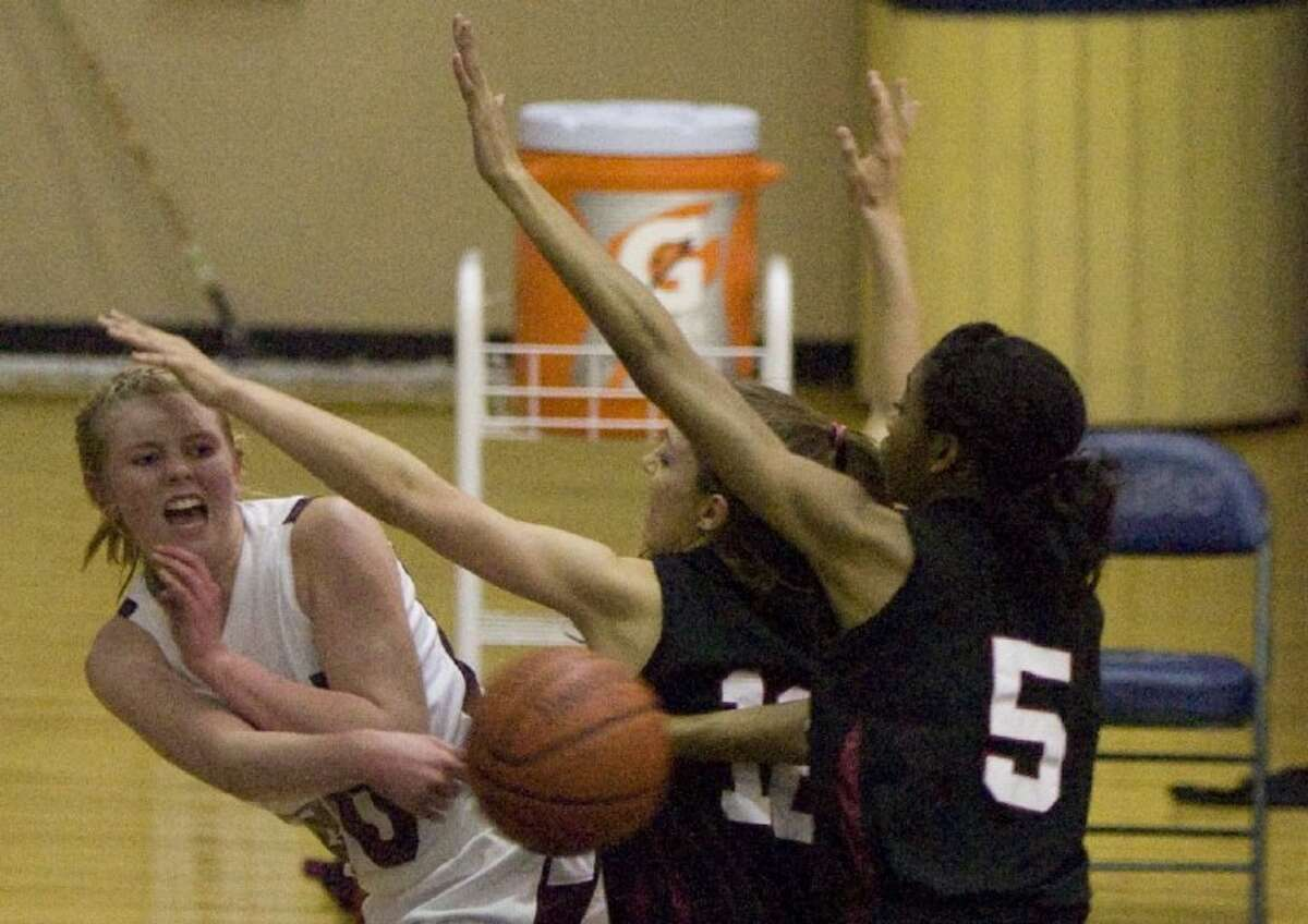 Magnolia's Caitlin Lawrence passes as she comes under pressure from Porter's Codie Swinhoe (12) and Sydney Williams (5) during Tuesday's Region III-4A bi-district playoff game at College Park High School.