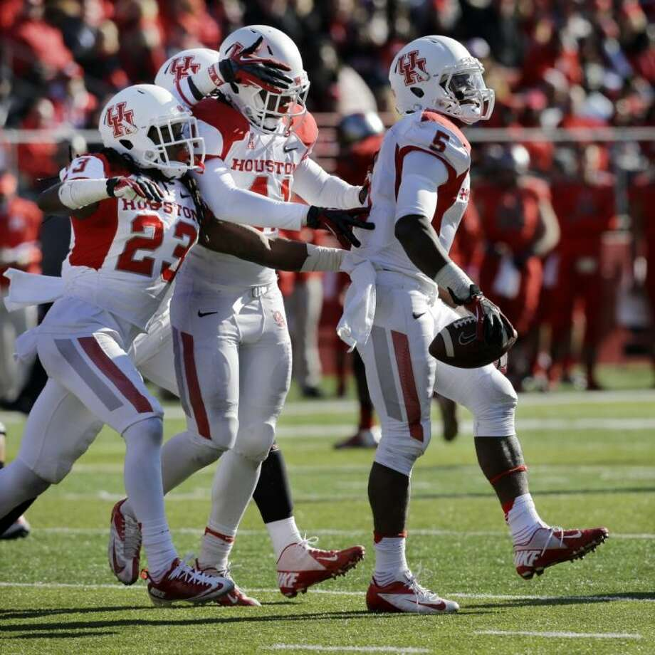Houston teammates celebrate with defensive back Turon Walker (5) after he made an interception against Rutgers on Saturday in Piscataway, N.J. The Cougars won 49-14.