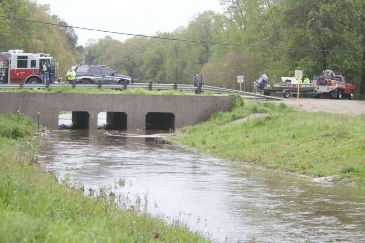 Emergency crews look for two missing children in a drainage canal intersecting Sorters Road in Porter on Sunday. The two boys were able to safely get to shore.