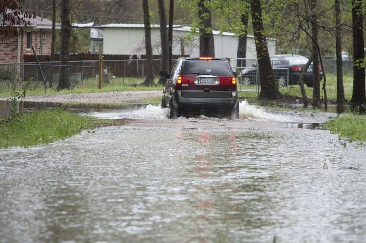 A vehicle drives down a flooded portion of Woodridge Circle near FM1314 on Sunday.