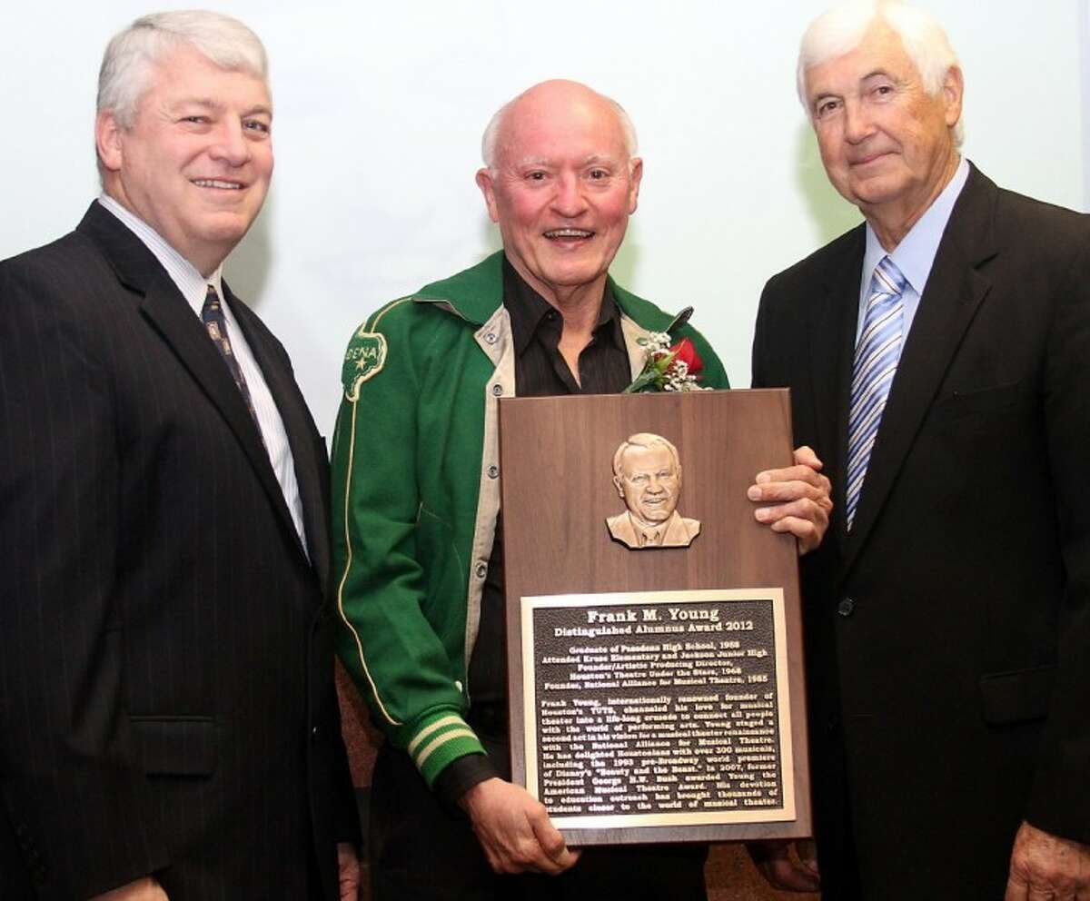 Frank Young displays his Distinguished Alumnus plaque with Superintendent Dr. Kirk Lewis and Board of Trustees member Marshall Kendrick.