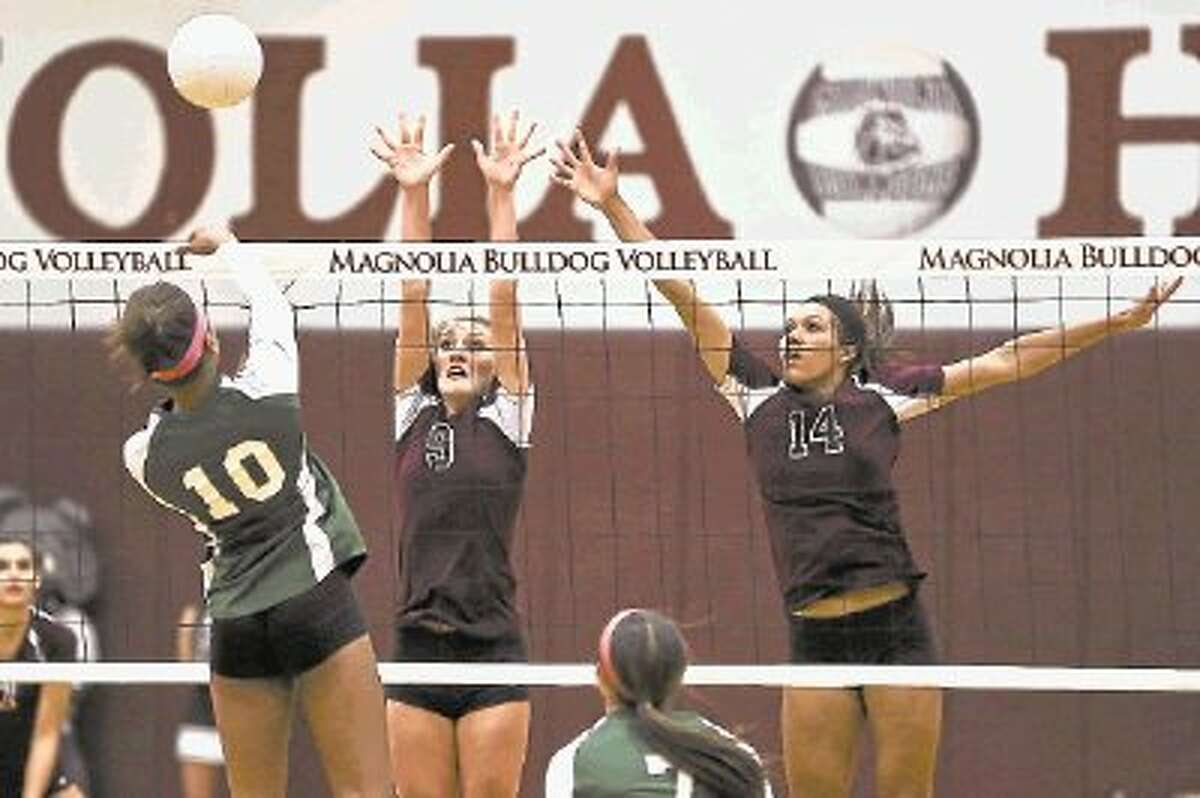 Magnolia's Kerstin Jenkins, right, and Brooke Harris go up for a block during a match against Huntsville on Tuesday at Magnolia High School. To view or purchase this photo and others like it, visit HCNpics.com.