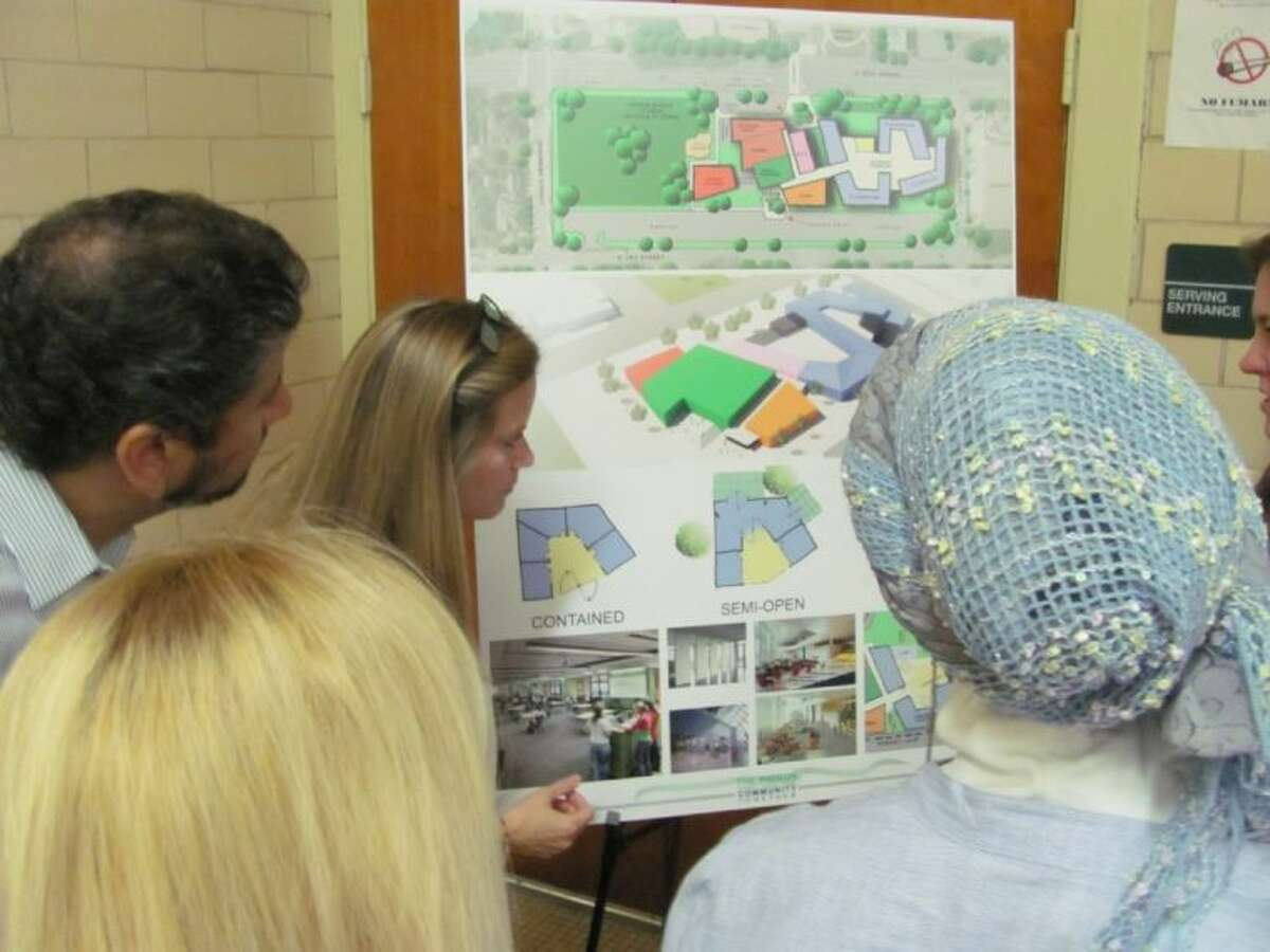 Condit Elementary School teacher Lenette Pruetz (at the design board) explains features included in the proposed design for the rebuilt school at a recent meeting to obtain community feedback.