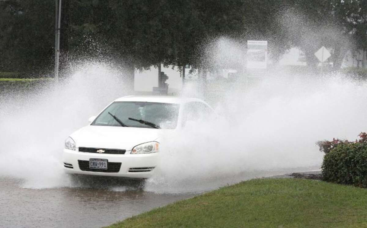 A car drives through the high water along Briar Forest Drive next to Paul Revere Middle School in Houston on Thursday, October 31. The rain pattern has is slowly yielding to a beautiful sky for trick or treaters.