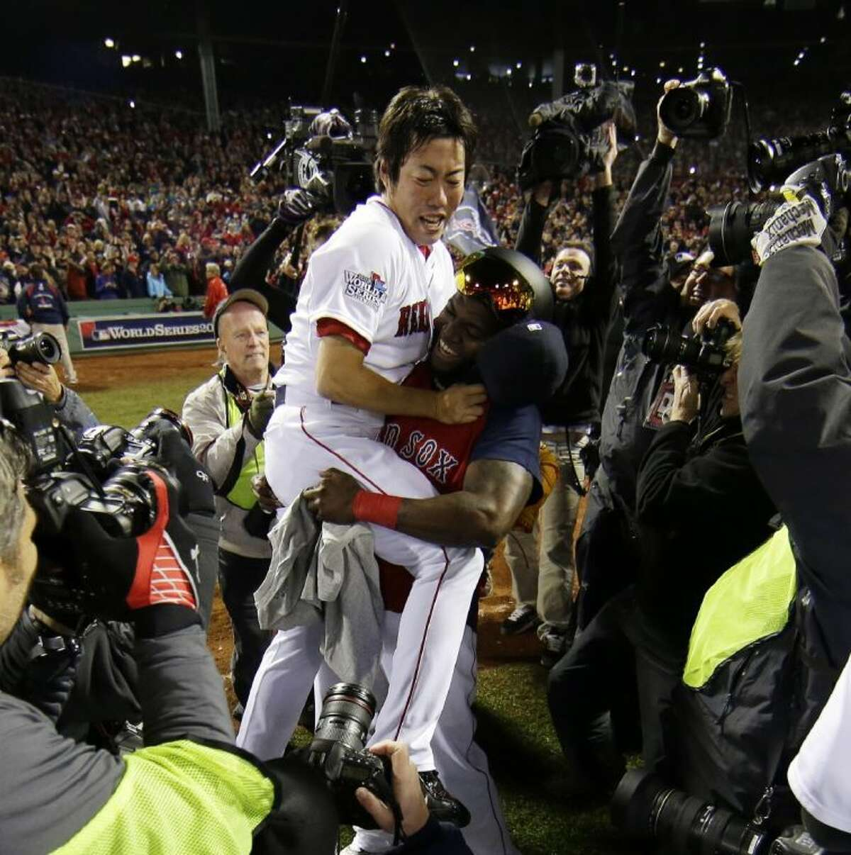 David Ortiz of the Red Sox hoists teammate Koji Uehara after they closed the World Series with a 6-1 victory over St. Louis.