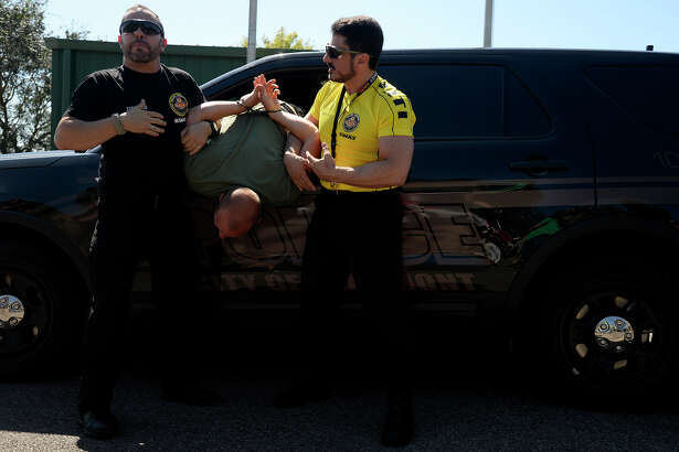 Fernando Carvalho, left, and Marcos Do Val, instructors with Brazilian police training company CATI, demonstrate handcuffing a driver through a car window on Wednesday. CATI was teaching immobilization techniques to SWAT and Special Response Team officers with Beaumont Police Department and the Orange County Sheriff's Office.  Photo taken Wednesday 9/28/16 Ryan Pelham/The Enterprise