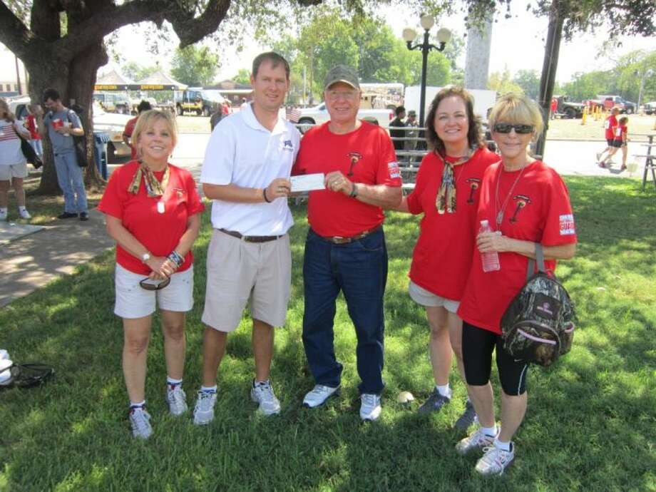 Kingwood Fallen Heroes Memorial Golf Tournament Director Scott Mitchell, who is also a Kingwood High School graduate, presents a check to Operation Military Embrace organization.