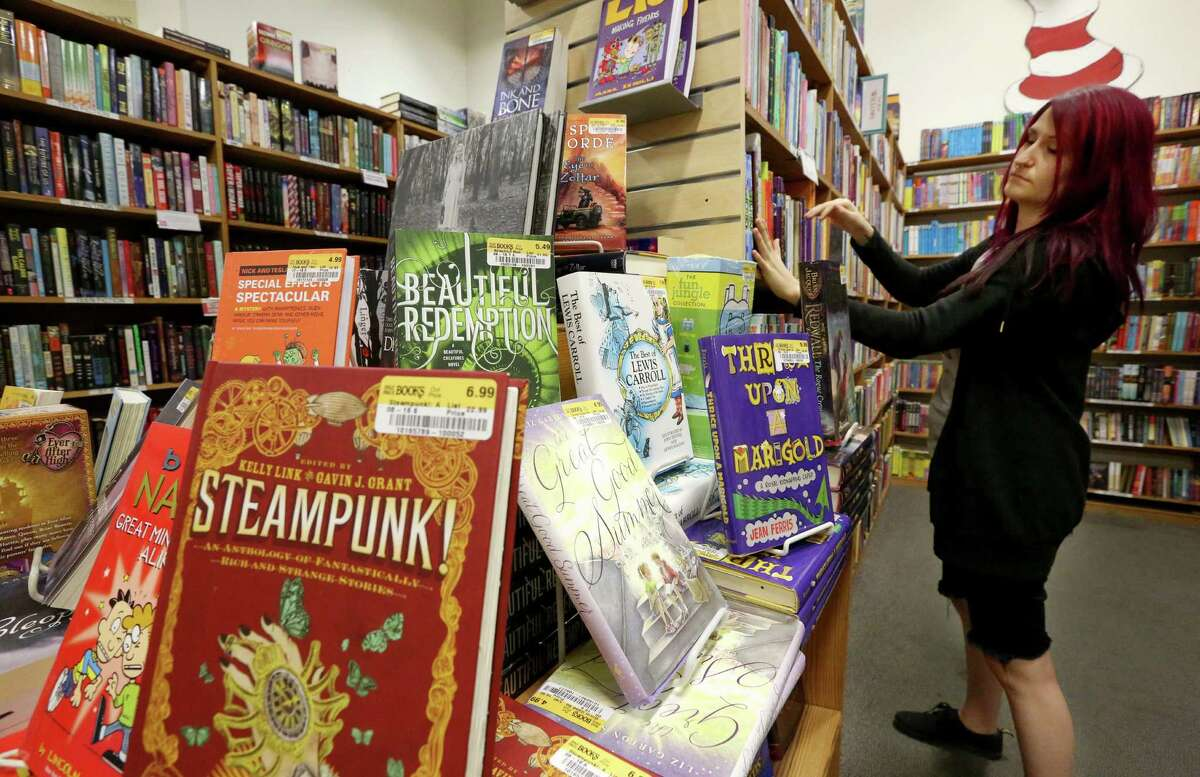 Half Price Books employee Nicole Malek organizes the bookstore's young adults section in Montrose Friday, Sept. 16, 2016, in Houston. Half Price Books stores have been expanding the young adults section as a strategy to attract more readers. ( Yi-Chin Lee / Houston Chronicle )