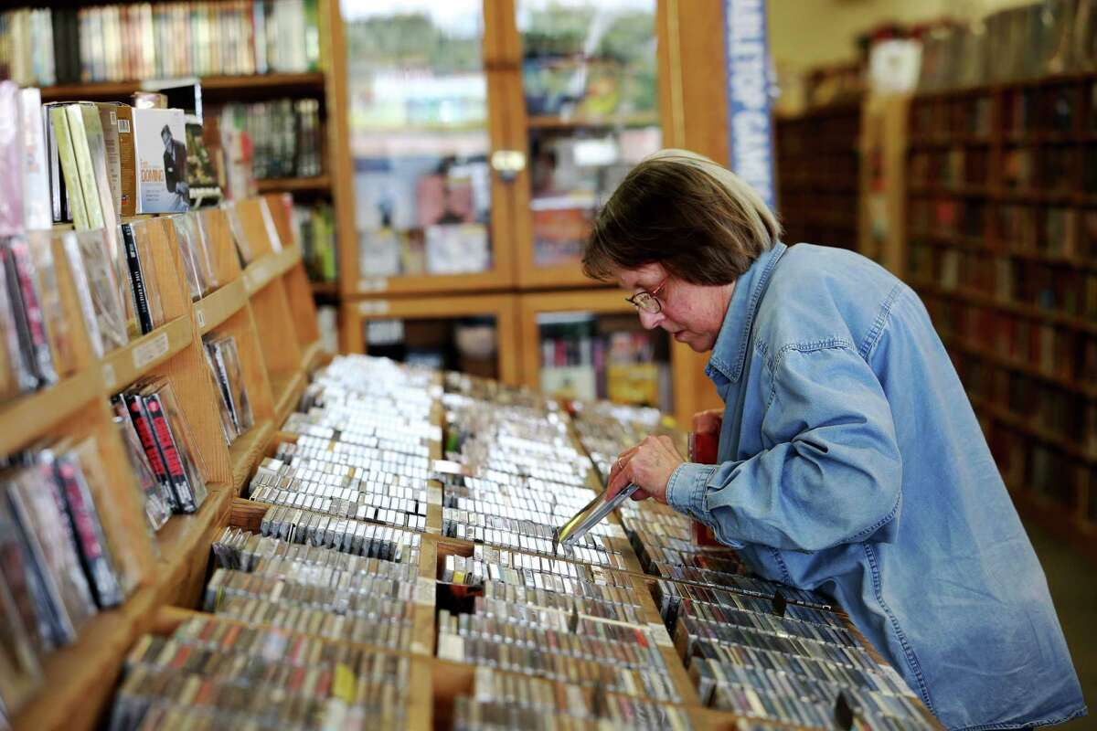 Patricia Powers goes through the CDs at Half Price Books vinyl section in Montrose Friday, Sept. 16, 2016, in Houston. Bookshops in the Houston area are temporarily closing, reducing hours and canceling events in response to the novel coronavirus pandemic.