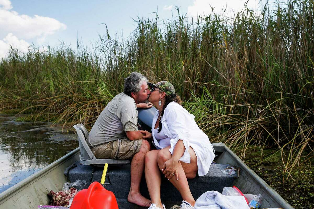 After freeing the boat from water hyacinth, Mike returns sopping wet to the boat. Relieved that he wasn't attacked by a gator, Nancy kisses him.