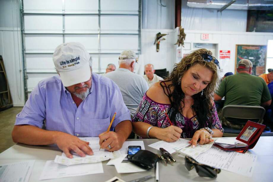 Mike and Nancy fill out paperwork for the alligator hunt. Photo: Michael Ciaglo, Houston Chronicle / © 2016  Houston Chronicle
