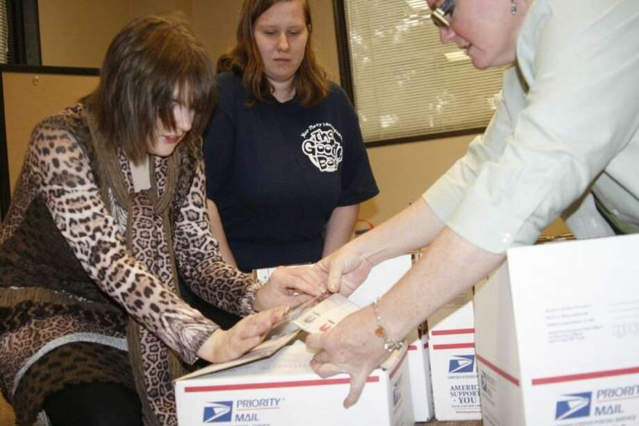Autumn's Dawn Education Specialist Jennifer Orenic, right, helps clients Autumn's Dawn clients Autumn Howard and Melissa Andrews pack up supplies to send to troops serving overseas.