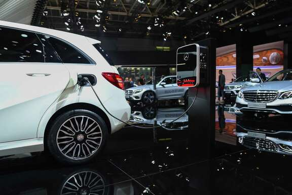 A Mercedes B250e electric automobile, manufactured by Mercedes-Benz AG, is connected to a charging station at the Paris Motor Show. A quarter of the world's cars will be an electric by 2040, according to BNEF. Manufacturers from Toyota Motor Corp. to General Motors Co. are joining Elon Musk's Tesla Motors Inc. in developing new models.