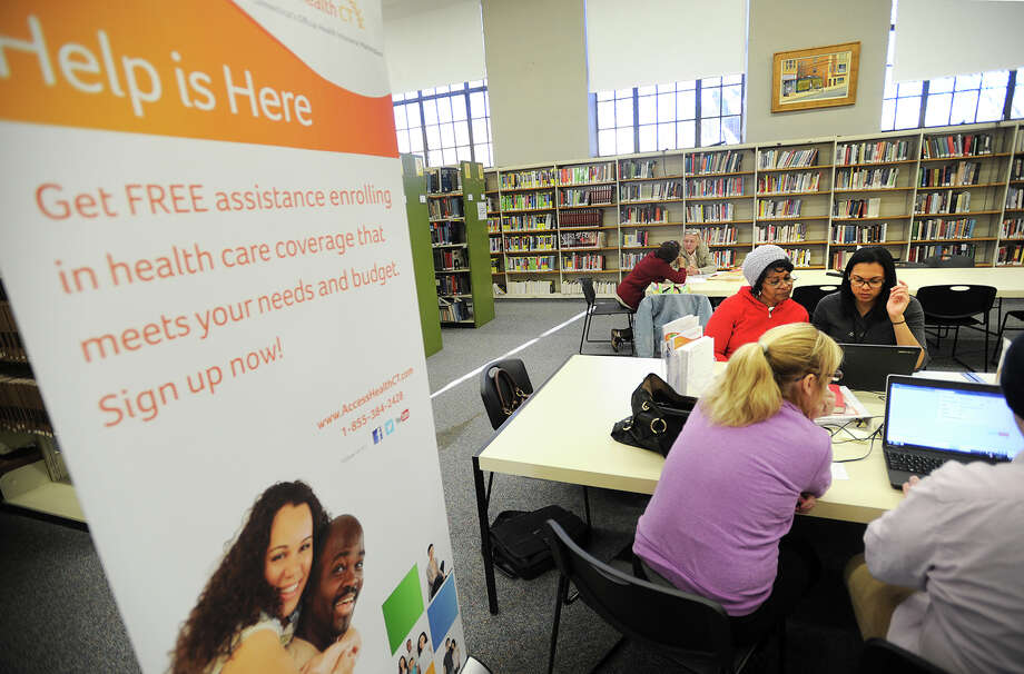 Representatives from Access Health CT help residents sign up for health insurance at the Bridgeport Public Library at 925 Broad Street in downtown Bridgeport, Conn. on Tuesday, November 18, 2014. The service will be available on the library's second floor, Tuesdays through Saturdays until February 15, 2015, beginning each day at 10:30 am. Photo: Brian A. Pounds / Brian A. Pounds / Connecticut Post