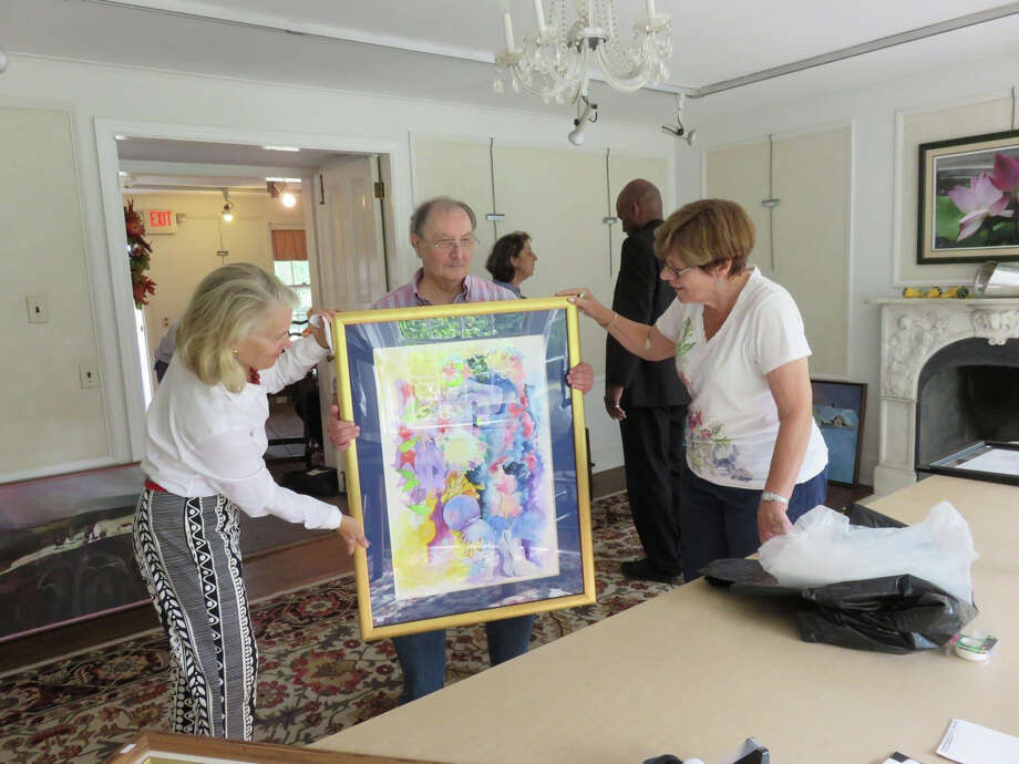 Richter Art Association's 38th Annual Juried Art Show opens Saturday, Oct. 1, from 2 p.m. to 5 p.m. at Richter House in Danbury. Seen here, from left, are board members Susan Roberts and Arline Corcoran as they examine Dominick Tomanelli's entry on receiving day for the 2015 show. Photo: Contributed Photo