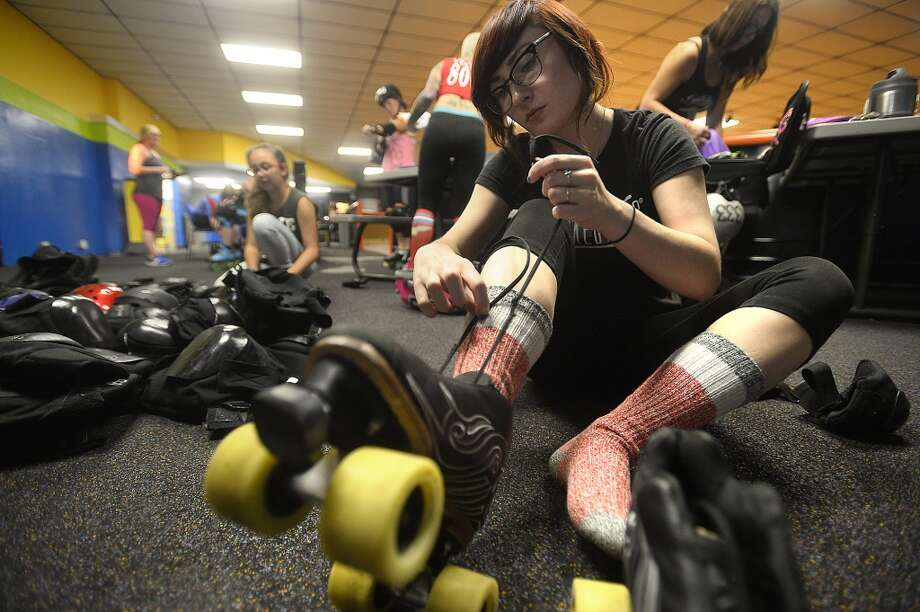 Lauriann Beggs, who hopes to eventually join the derby team, laces up as the Spindletop Rollergirls and team trainers kicked off their Beginners Boot Camp Monday night at Manning's Texas on Wheels Skating Rink in Beaumont. The six-week course, which is held Monday and Wednesday nights, offers skating instruction, how to fall properly and stop, as well as the rules and strategies of roller derby. Participants will not only learn more about the sport, but can advance to the recreation league, and eventually try out to join the team, which competes throughout the region. Roller derby continues to thrive since the sport saw a resurgence in popularity in the 1990's.  Photo taken Monday, September 19, 2016 Kim Brent/The Enterprise Photo: Kim Brent/The Enterprise