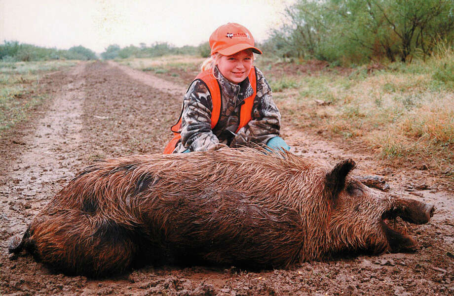 A girl grins while checking out a large feral hog she harvested on a hunt conducted by the Texas Youth Hunting Program, which has taken 17,000 kids hunting since 1996. Photo: Courtesy Photo / Courtesy Photo