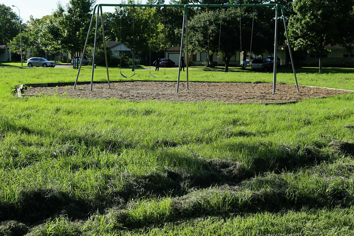 High grass surrounding a swing set at Oak Meadow Park Sept. 29, 2016, in Houston. ( James Nielsen / Houston Chronicle )