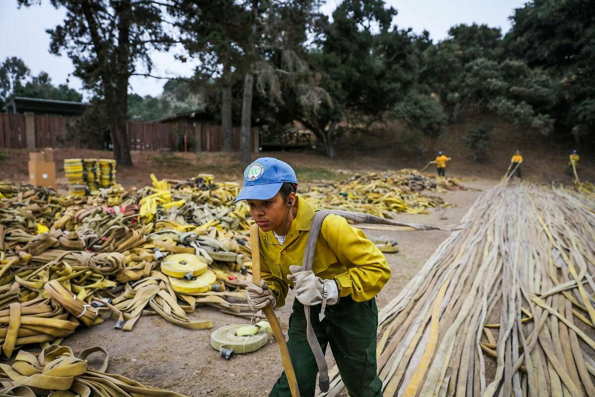 Alyssa Mae Sultana, who is in training for disaster relief with California Conservation Core, pulls a firehose while organizing materials, at Toro base camp, which acts as home base for firefighters and support teams who are fighting the Soberanes Fire, in Salinas, California, on Thursday, Sept. 29, 2016.