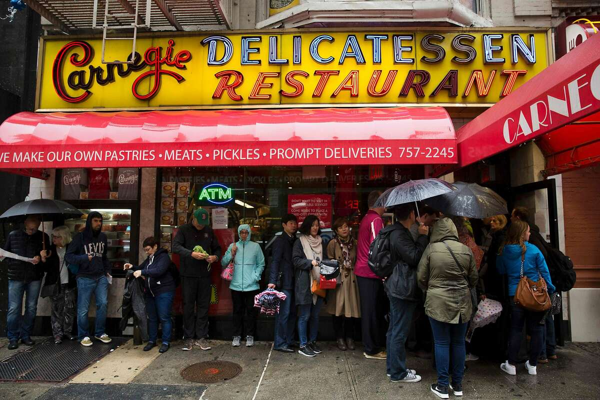 Patrons line up in the rain at the Carnegie Deli on September 30, 2016, in New York. The internationally known restaurant icon closed at the end of 2016.