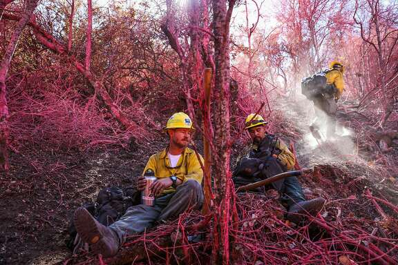 Firefighters John Waybright (left), Pedro Rios (center) and Brent Panos (right) take a lunch break from traversing a forested area while looking for hot spots caused by the Soberanes Fire, in Monterey, California, on Thursday, Sept. 29, 2016.