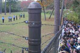 Fort Benning law enforecment, left, line up and watch for protesters through the fence who want to trespass on Fort Benning during the 14th Annual School of Americas Watch Protest, Sunday, Nov. 23, 2003, in Columbus, Ga. The protest aims to close the Western Hemisphere Institute of Securty Cooperation, once known as the School of the Americas, claiming it teaches torture tactics to Latin American Armies and human rights violations. (AP Photo/Columbus Ledger-Enquirer, G. Marc Benavidez)