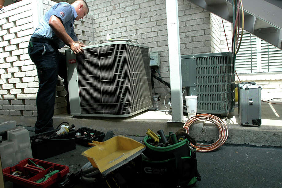 A Jon Wayne Heating & Air technician repairs an air conditioning unit in this 2009 file photo. Photo: BETH SPAIN /SPECIAL TO THE EXPRESS-NEWS / SAN ANTONIO EXPRESS-NEWS