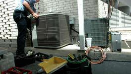 A Jon Wayne Heating & Air technician repairs an air conditioning unit in this 2009 file photo.