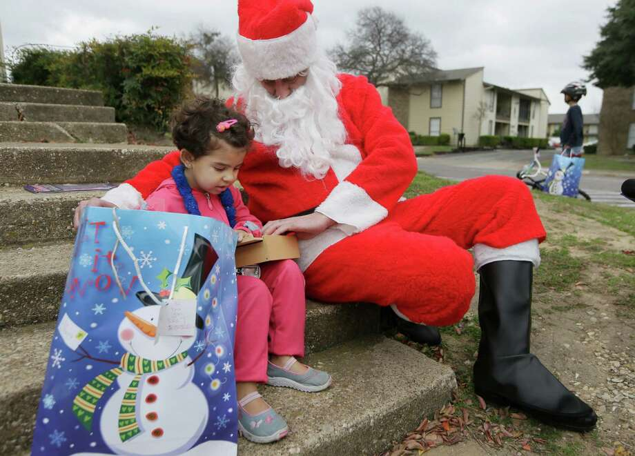 Newly arrived Syrian refugee Jory, 4, left, receives a gift outside her family's apartment from volunteer Tim Blystone, right, portraying Santa Claus Dec. 12, 2015, in Dallas. Photo: LM Otero /Associated Press / AP
