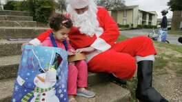 Newly arrived Syrian refugee Jory, 4, left, receives a gift outside her family's apartment from volunteer Tim Blystone, right, portraying Santa Claus Dec. 12, 2015, in Dallas.