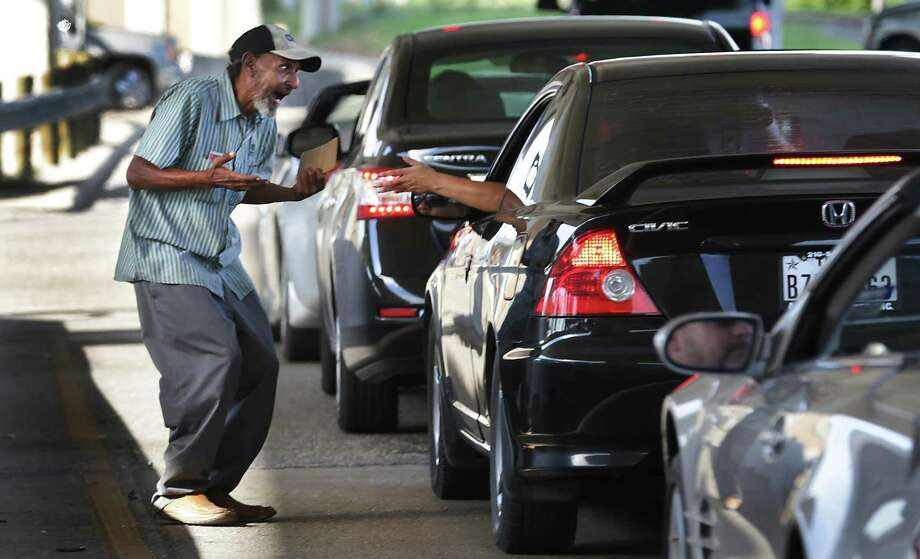 Jose Losoya, 57, reacts as a woman, who said she was once homeless, gives him money at the exit ramp of I 10 to Woodlawn Rd. on Sept. 22. Losoya said he uses most of the money collected for food and clothing but admitted he spends around $20 a week on beer. Photo: BOB OWEN /San Antonio Express-News / © 2014 San Antonio Express-News