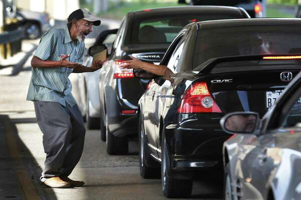 Jose Losoya, 57, reacts as a woman, who said she was once homeless, gives him money at the exit ramp of I 10 to Woodlawn Rd. on Sept. 22. Losoya said he uses most of the money collected for food and clothing but admitted he spends around $20 a week on beer.