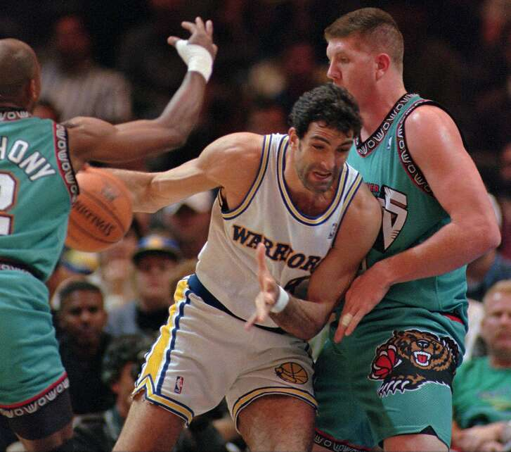 Golden State Warriors center Rony Seikaly, center, drives to the basket past Vancouver Grizzlies center Bryant Reeves, right, during the first quarter, Tuesday, March 5, 1996 at the Oakland, Calif., Coliseum Arena. At left is Grizzlies guard Greg Anthony. (AP Photo/Andy Kuno)