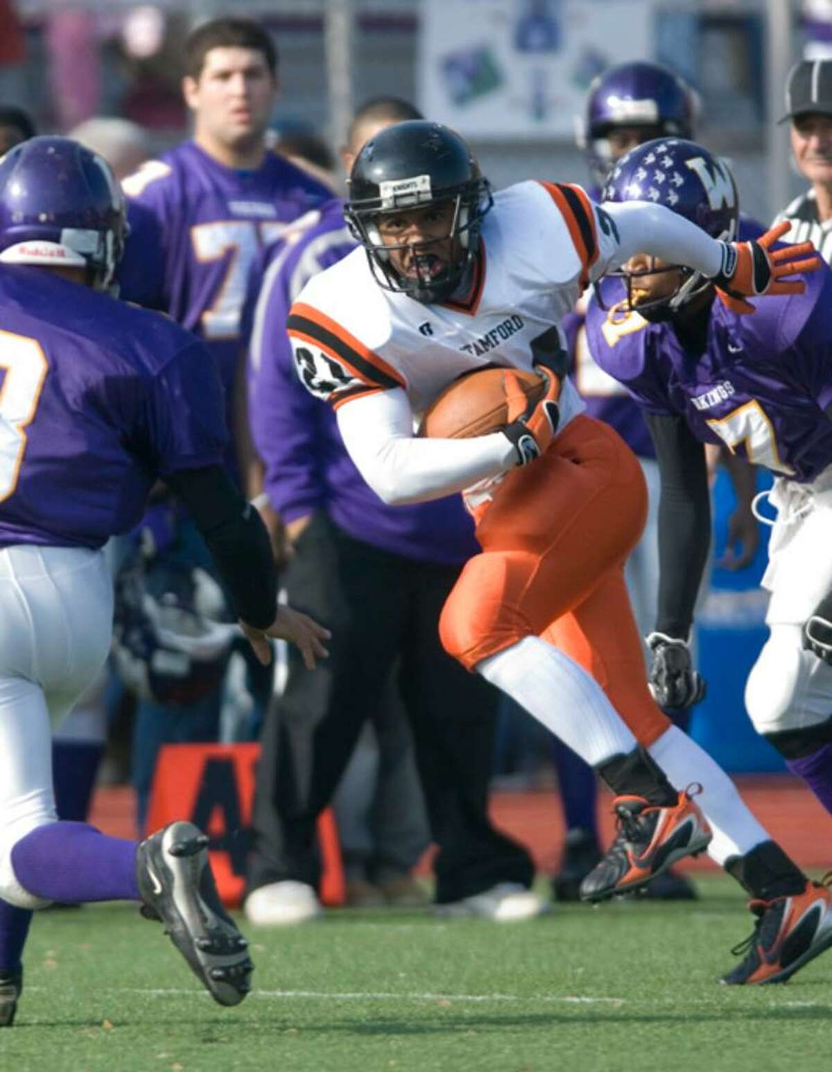 Stamford_112307_ Stamford's Marcus Dixon, right, runs the ball downfield, while Westhill's Ronald Thompson, left, looks to make a tackle during a football game at Westhill High School in Stamford, Conn. on Thanksgiving Day, Thursday, Nov. 22, 2007. Chris Preovolos/Staff photo Staff Photo Chris Preovolos
