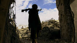 KANDAHAR, 2001: FOR METRO DAILY - An armed Hamid Karzai guard carries his rifle through the bombed out remains of what was Mullah Omar's compound in Kandahar, Afghanistan Wednesday Dec. 12, 2001. MANDATORY PHOTO CREDIT EDWARD A. ORNELAS/SAN ANTONIO EXPRESS-NEWS HEARST NEWSPAPERS. WITH JOHN OTIS STORY.