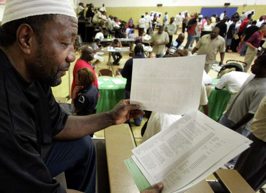 "A job seeker scans a list of potential employers at a job fair for ex-convicts in Dallas. Most employers require job seekers to check a box on an application indicating whether they have a criminal record. This can function as an ""application denied."" Photo: Associated Press / File Photo / AP"