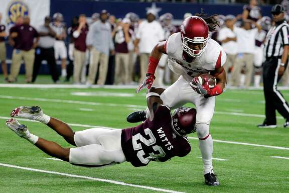 Texas A&M defensive back Armani Watts (23) stops Arkansas wide receiver Keon Hatcher on fourth down late in the second half on Sept. 24, 2016, in Arlington.