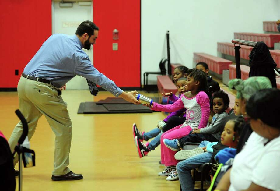 Housatonic Community College's Andrew Pelletier hands out a HCC travel mug to one of the kids at the Trumbull Gardens Multi-Purpose Center in Bridgeport, Conn. on Thursday Sept. 29, 2016. The president and some staff at HCC came to the center to officially announce the start of a tutoring program for the kids. Trumbull Gardens has been the site of plenty of violence and this program is much needed, especially since the community center was shuttered for a while and just recently reopened. The program, which starts in October, will be held every Tuesday, Wednesday and Thursday from 3:30 p.m. to 6 p.m. Photo: Christian Abraham / Hearst Connecticut Media / Connecticut Post
