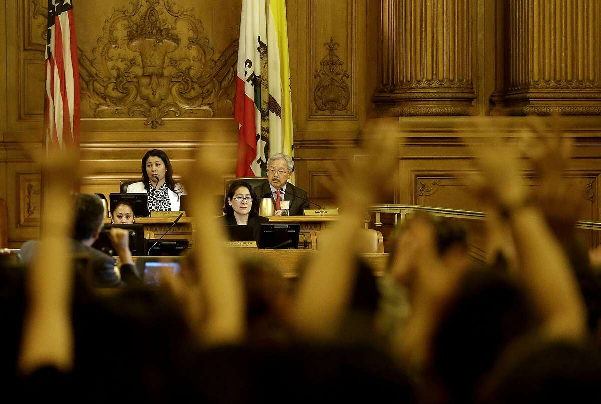 Protesters react by raising their arms as San Francisco Mayor Ed Lee, center, speaks during a Board of Supervisors meeting at City Hall in San Francisco, Tuesday, May 10, 2016. (AP Photo/Jeff Chiu)