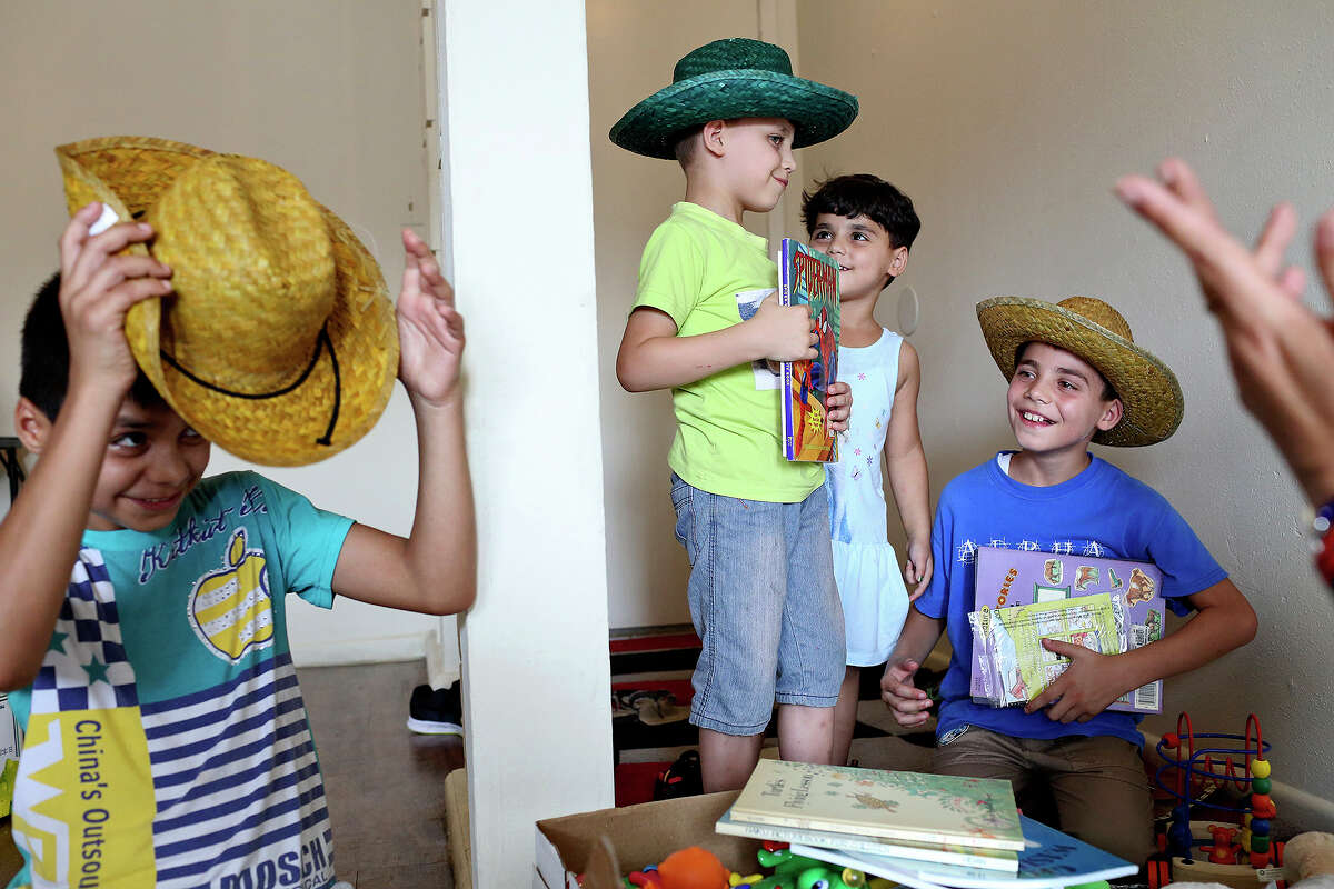 Syrian refugees Hamdo, 12 (from left), Mohammed, 6, Huda, 4, and Hassan, 10, explore a box of toys given to their family by refugee advocate Pamela Espurvoa- Allen.