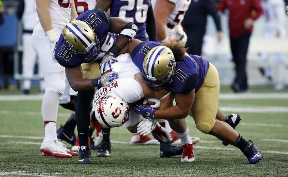 Stanford running back Christian McCaffrey (5) is tackled by Washington linebacker Azeem Victor (36) and defensive lineman Elijah Qualls in the first half of an NCAA college football game, Friday, Sept. 30, 2016, in Seattle. (AP Photo/Ted S. Warren) Photo: Ted S. Warren, Associated Press