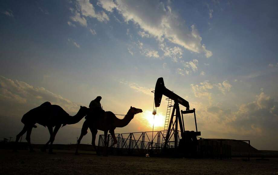 FILE- In this Sunday, Dec. 20, 2015 file photo, a man rides a camel through the desert oil field and winter camping area of Sakhir, Bahrain. OPEC nations have agreed in theory that they need to reduce their production to help boost global oil prices during a meeting in Algeria, but a major disagreement between regional rivals Saudi Arabia and Iran still may derail any cut. (AP Photo/Hasan Jamali, File) Photo: Hasan Jamali, STR / Copyright 2016 The Associated Press. All rights reserved.