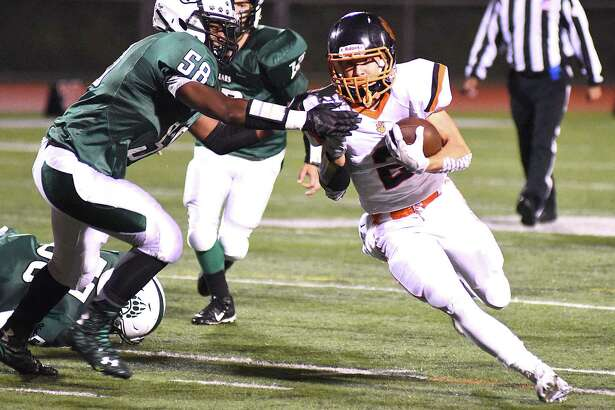 Ridgefield running back Shane Palmer (2) runs up field with the ball as Norwalk's Niar Brown defends during Friday's game at Testa Field in Norwalk.