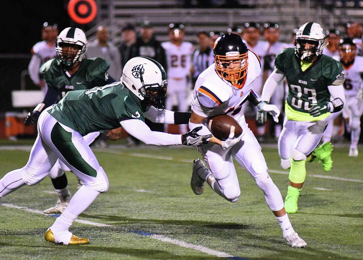 Ridgefield wide receiver Christopher Longo looks for yards after a catch as Norwalk defenders Akber Khan, left, and Marco Monteiro move in during the first half of Friday's FCIAC football game in Norwalk.