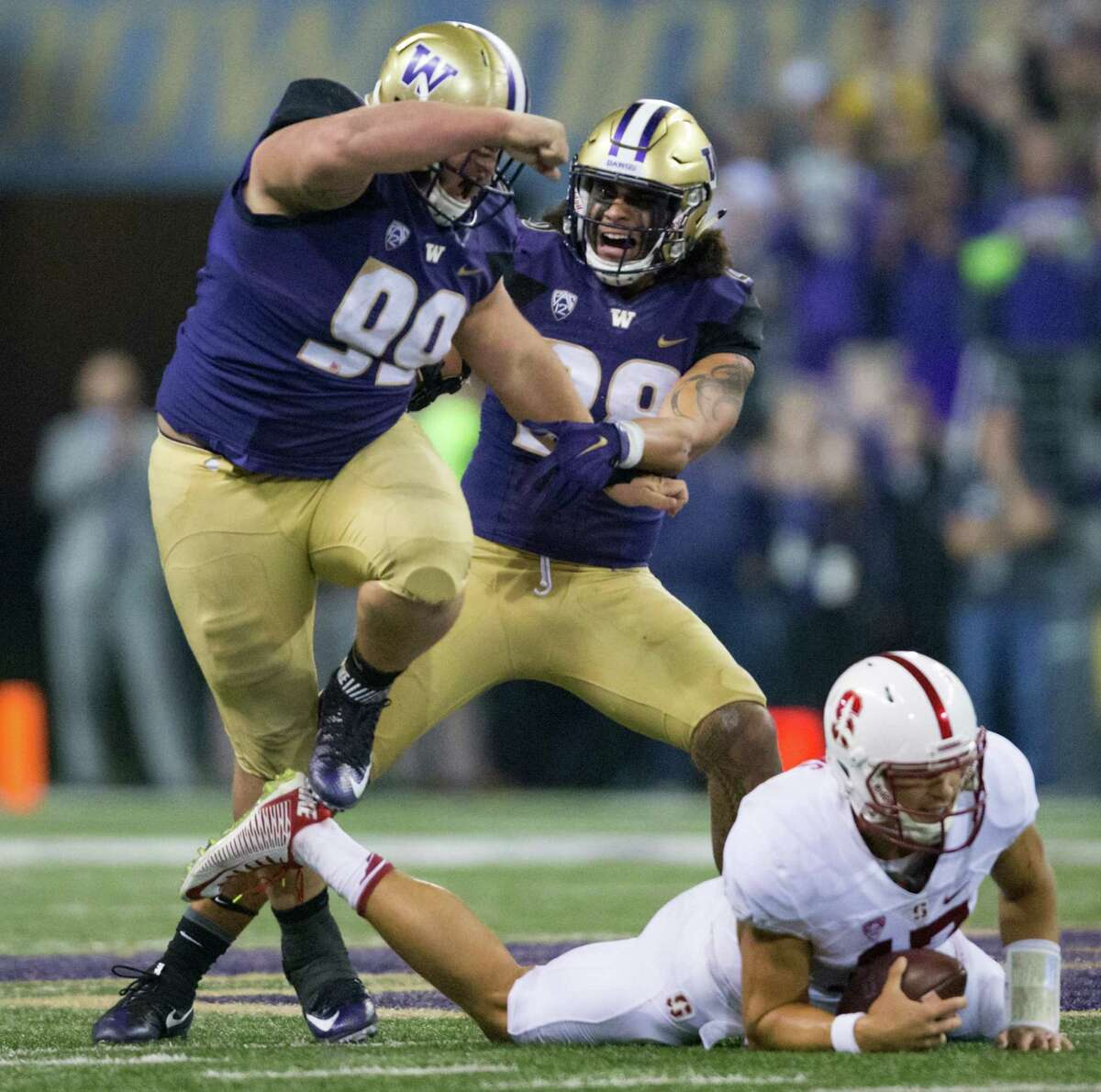University of Washington Linebacker Psalm Wooching joins defensive lineman Greg Gaines in celebration after Gaines tackled Stanford quarterback Ryan Burns in the second quarter at Husky Stadium, Friday, Sept. 30, 2016.