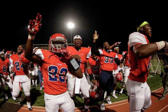 Alief Taylor Lions Jesse Walker (22) and Alief Taylor Lions quarterback Dontay Warren (8) celebrate with teammates after the high school football game between the Pearland Oilers and the Alief Taylor Lions at Crump Stadium in Houston, TX on Friday, September 30, 2016.  The Lions defeated the Oilers 19-14.