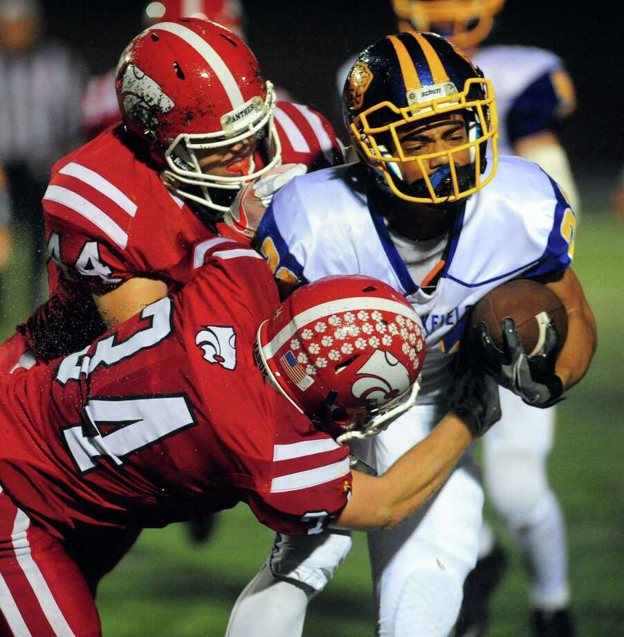 Brookfield's Samuel Jackson is taken down by Masuk's Andrew Ciancetta, top left, and Jack Roberge during football action in Newtown, Conn. on Friday Sept. 30, 2016. Photo: Christian Abraham / Hearst Connecticut Media / Connecticut Post